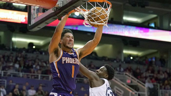 FILE - In this Jan. 5, 2020, file photo, Phoenix Suns guard Devin Booker (1) dunks over Memphis Grizzlies forward Jaren Jackson Jr. in the second half of an NBA basketball game in Phoenix. Booker won the NBA 2K20 Players Tournament on Saturday, April 11, 2020, sweeping Suns teammate Deandre Ayton in the best-of-three final. (AP Photo/Rick Scuteri, File)