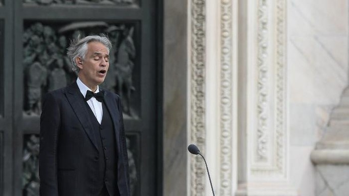 Italian tenor and opera singer Andrea Bocelli sings during a rehearsal on a deserted Piazza del Duomo in central Milan on April 12, 2020, prior to an evening performance without public for the world wounded by the pandemic, during the countrys lockdown aimed at curbing the spread of the COVID-19 infection, caused by the novel coronavirus. (Photo by Piero Cruciatti / AFP)