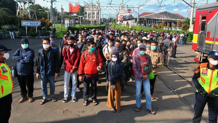 Sejumlah penumpang KRL Commuter Line antre menunggu kedatangan kereta di Stasiun Bogor, Jawa Barat, Senin (13/4/2020). Antrean panjang penumpang KRL Commuter Line di Stasiun Bogor tersebut akibat kebijakan pemeriksaan suhu tubuh dan pembatasan jumlah penumpang di setiap rangkaian kereta sebagai tindakan pencegahan penyebaran wabah pandemi virus Corona (COVID-19). ANTARA FOTO/Arif Firmansyah/hp.