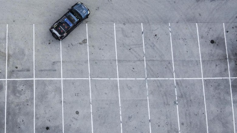 An aeriel view shows Italian chef Aldo Giaquinto and his wife Vera Kozlovskaia parking their car in a Walmart parking lot in Miami, on April 10, 2020. - The couple has lived for the past two weeks camped out in their converted Toyota Land Cruiser in a Walmart parking lot. (Photo by CHANDAN KHANNA / AFP)