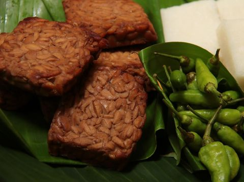 Tempe Bacem, the traditional Javanese dish of tempeh (soy bean cake) braised in soy sauce. A popular accompaniment for many other Javanese dish, such as with Jadah, the glutinous rice and coconut cake. The dish are placed on a woven bamboo tray lined with banana leaf. Jadah tempe are eaten with fresh green chili pepper.