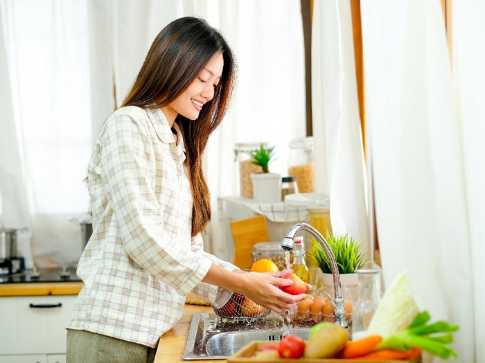 Asian beautiful teen girl is washing the apple and other fruit in the kitchen and look happy.