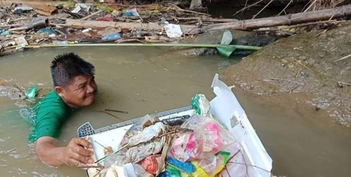 Wahyudi saat mengangkut sampah di sungai (dok. Istimewa)