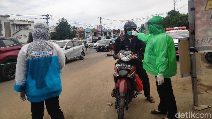 Pengecekan kesehatan dilakukan kepada pengguna jalan yang hendak masuk ke Kota Makassar (M Taufiqqurrahman/detikcom)