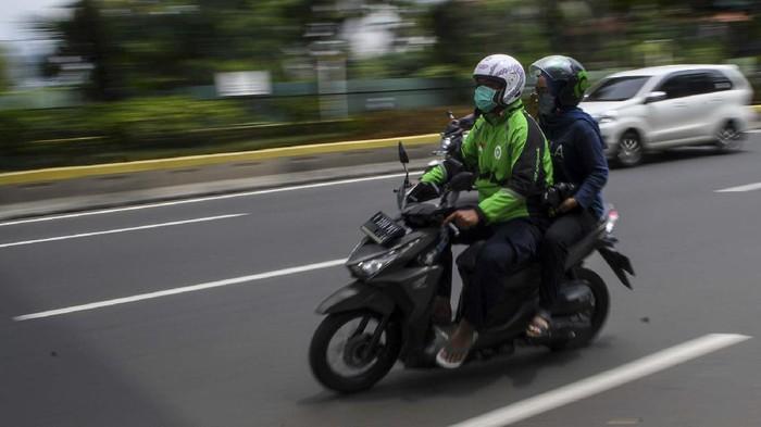 Pengemudi ojek daring membonceng penumpang saat melintas di kawasan Kramat Raya, Jakarta, Senin (13/4/2020). Pelaksana tugas (Plt) Menteri Perhubungan Luhut Pandjaitan mengizinkan ojek daring mengangkut penumpang selama masa Pembatasan Sosial Berskala Besar (PSBB) di Jakarta, namun dengan ketentuan harus memenuhi protokol kesehatan yang ditetapkan. ANTARA FOTO/M Risyal Hidayat/wsj.