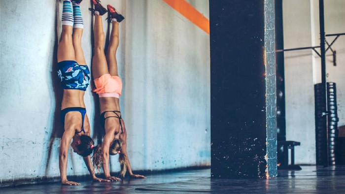 Women performing handstand in gym.  Professional sportists. Wearing sports clothing.