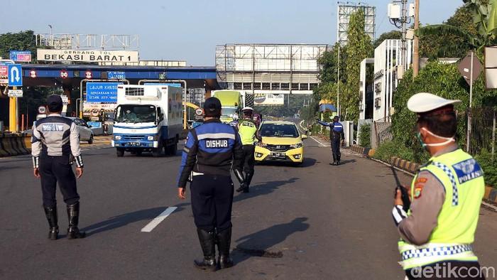 Petugas gabungan dari Dishub Pemkot Bekasi dan polisi pantau lokasi pengecekan penerapan PSBB. Lokasi check point itu berada di Gerbang Tol Bekasi Barat.