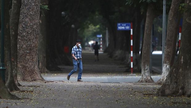 A man wearing a face mask walks on a quiet street in Hanoi, Vietnam, Wednesday, April 1, 2020. Vietnam on Wednesday starts two weeks of social distancing to contain the spread of COVID-19. The new coronavirus causes mild or moderate symptoms for most people, but for some, especially older adults and people with existing health problems, it can cause more severe illness or death. (AP Photo/Hau Dinh)