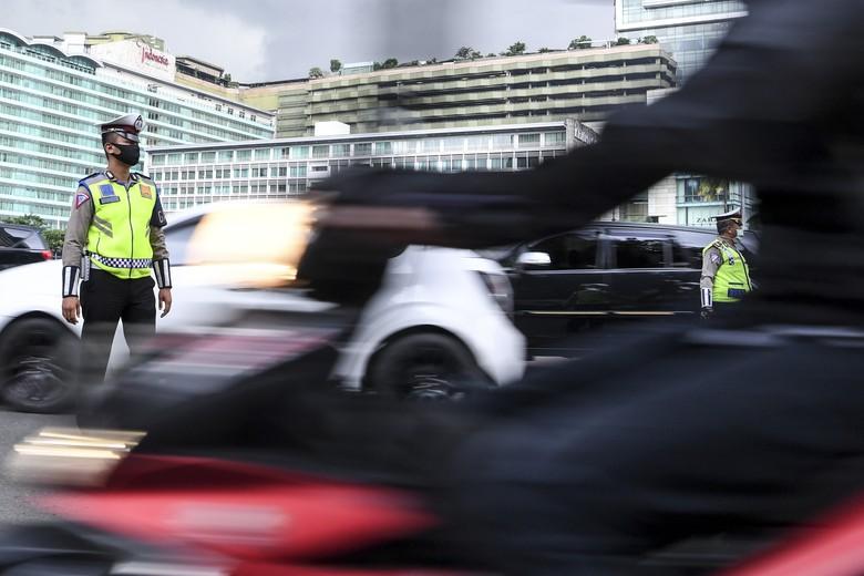 Satpol PP meminta pengendara motor mengenakan masker saat pemeriksaan kepatuhan Pembatasan Sosial Berskala Besar (PSBB) di kawasan Bundaran HI, Jakarta, Senin (13/4/2020). Pemeriksaan tersebut untuk memastikan setiap pengendara mobil dan motor mematuhi aturan PSBB yang diterapkan di DKI Jakarta. ANTARA FOTO/Hafidz Mubarak A/wsj.
