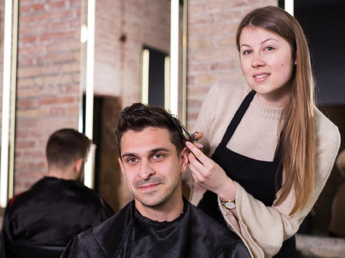 Young skillful woman barber making hairstyle for male client in hair studio