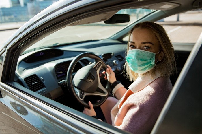 Woman in protective mask driving a car on road. Safe traveling.