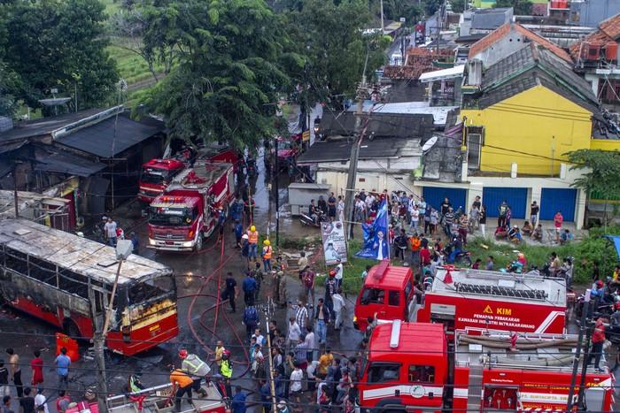 Petugas pemadam kebakaran melakukan pendinginan usai memadamkam api  pada bus karyawan PO Warga Baru yang terbakar di Jalan Raya Cidomba, Telukjambe Timur, Karawang, Jawa Barat, Selasa (14/4/2020). Kecelakaan bus yang membawa karyawan tersebut terbakar setelah menabrak enam kios dan hingga kini penyebab kecelakaan masih dalam penyelidikan pihak berwajib. ANTARA FOTO/M Ibnu Chazar/hp.