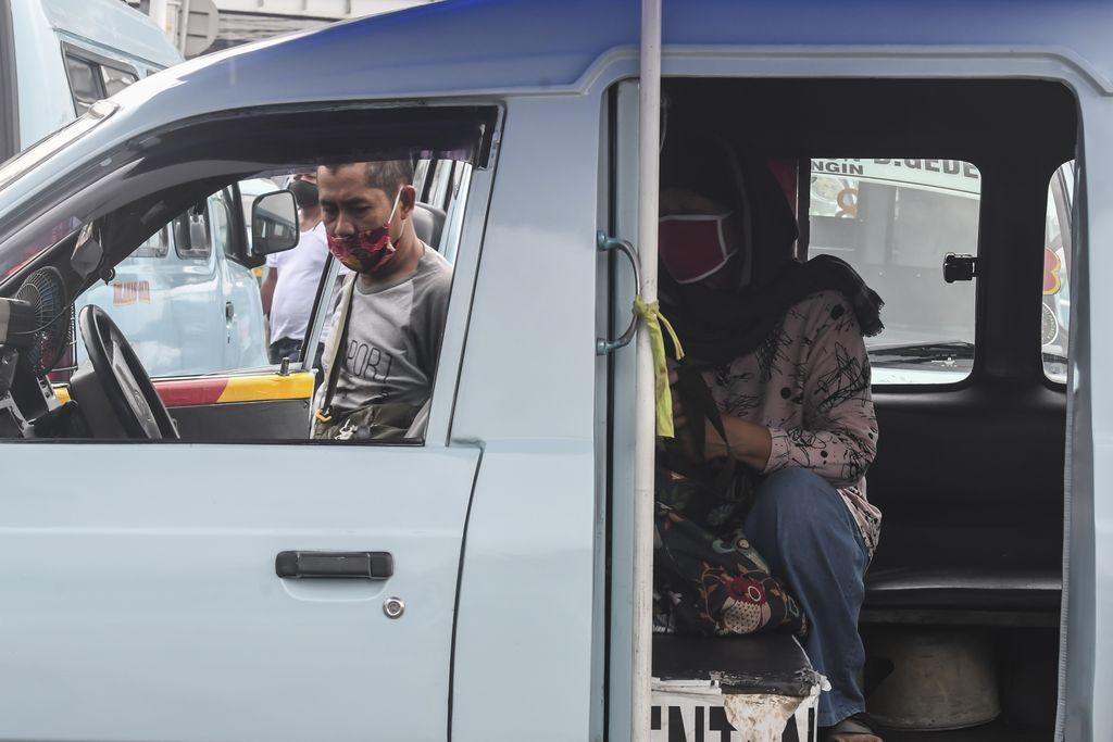Warga menumpang angkutan umum di Terminal Kampung Melayu, Jakarta, Rabu (15/4/2020). Ketua Organda DKI Shafruhan Sinungan mengatakan dari sekitar 85.900 kendaraan yang berada di bawah naungannya, hanya 8.000-8.600 unit yang masih dapat beroperasi hal tersebut disebabkan jumlah penumpang turun drastis karena sebagian besar orang kini lebih banyak di rumah mengikuti imbauan pemerintah dan penerapan PSBB. ANTARA FOTO/Muhammad Adimaja/aww.
