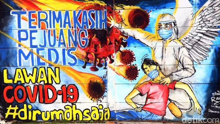 Seorang warga melintas di dekat Mural perjuangan Tim Medis melawan Covid-19 di daerah Limo, Kota Depok, Jawa Barat, Rabu (15/4/2020). Mural itu sebagai ucapan terima kasih kapada tim medis yang menangani pasien Corona.