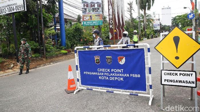 Petugas gabungan dari Dishub, Polisi dan TNI berjaga di kawasan Cinere yang merupakan perbatasan Kota Depok, Jawa Barat, Rabu (15/4/2020). Mulai hari ini Depok telah menerapkan pembatasan sosial berskala besar (PSBB)