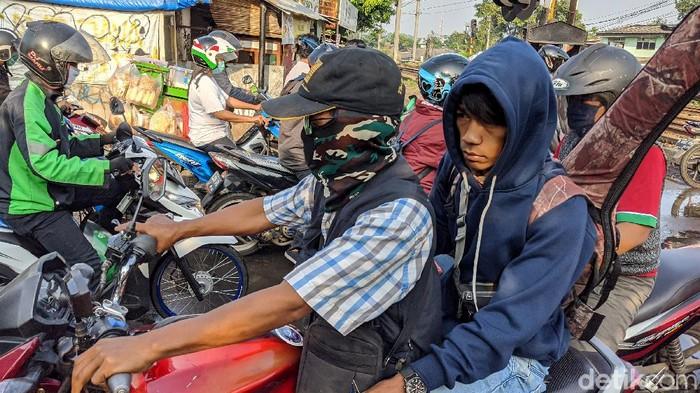 Sebagian pengendara sepeda motor dan sopir angkutan umum beraktifitas tanpa menggunakan masker pelindung di Jl Jombang-Sudimara,  Kota Tangerang Selatan.