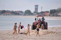 Petugas dengan traktor meminta wisatawan asing yang masih bandel maen di pantai untuk meninggalkan kawasan Pantai Kedonganan, Badung, Bali.
