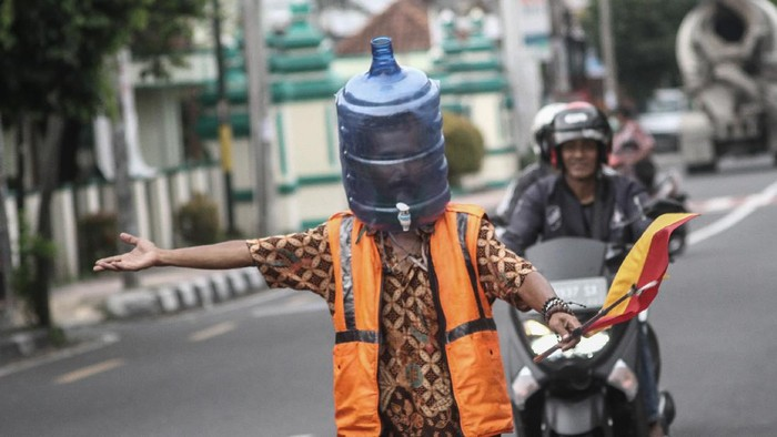 Ali Akbar (52) Sukarelawan Pengatur Lalu Lintas (Supeltas) mengatur lalu lintas mengenakan pelindung wajah dari galon bekas di Jalan Tamansiswa, DI Yogyakarta, Rabu (15/4/2020). Ali Akbar menggunakan pelindung wajah unik itu saat mengatur lalu lintas guna mengantisipasi penularan COVID-19. ANTARA FOTO/Hendra Nurdiyansyah/foc.
