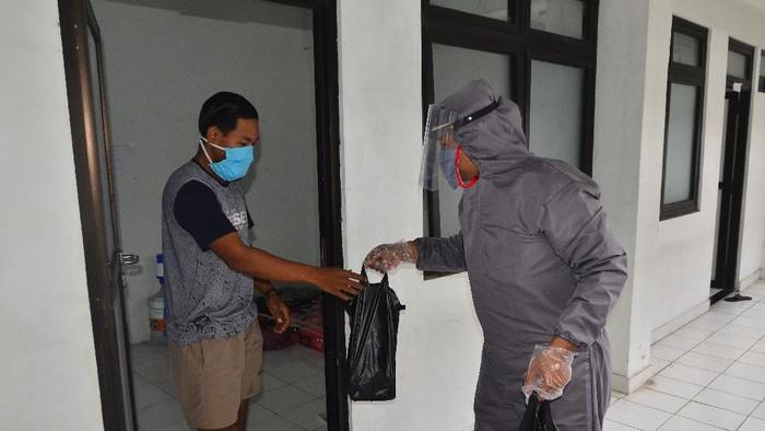 Petugas membagikan makanan kepada Orang Dalam Pemantauan (ODP) COVID-19 yang dikarantina di Rusunawa Bakalan Krapyak, Kudus, Jawa Tengah, Rabu (15/4/2020). Berbagai fasilitas diberikan pemerintah setempat kepada ODP yang sebagian besar para pemudik tersebut seperti kamar tidur dan kamar mandi pribadi, fasilitas kesehatan dan jaminan makan untuk kenyamanan ODP selama di karantina. ANTARA FOTO/Yusuf Nugroho/aww.
