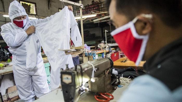 Penjahit memakai contoh pakaian alat pelindung diri (APD) untuk tenaga medis di Bandung, Jawa Barat, Senin (13/4/2020). Penjahit spesialis seragam dinas dan jaket ini mengalihkan produksinya ke pembuatan APD untuk tenaga medis dalam penanganan pasien COVID-19 di sejumlah rumah sakit umum dan swasta di Jawa Barat dengan jumlah produksi 300 hingga 400 buah per minggu.