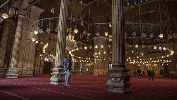 In this March 18, 2020 photo, an American tourist looks at the great Mosque of Muhammad Ali Pasha at the Citadel complex, in Cairo, Egypt. Like many other places in the world, the ripples of the worldwide coronavirus pandemic could end up drowning the vulnerable in Egypt. The partial lockdown threatens the livelihoods for many of Egypt's 100 million population, one of three of whom were already living in poverty, according to government figures. (AP Photo/Nariman El-Mofty)
