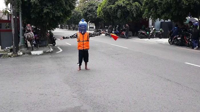 Kocak, pengatur lalu lintas di Yogyakarta, ini memakai galon air untuk menangkal virus Corona. Begini aksinya.