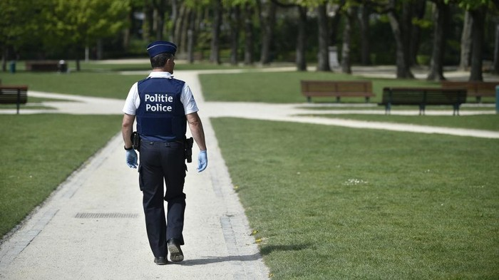 A police officer wearing protective gloves patrols in a park in Brussels on April 15, 2020 , as a strict lockdown has been in place for the past five weeks to stop the spread of COVID-19, the disease caused by the novel coronavirus. (Photo by JOHN THYS / AFP)