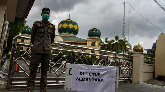Petugas Satpol PP Kota Pekanbaru berjaga di depan pintu masuk Masjid Agung Ar-Rahman yang ditutup sementara, di Pekanbaru, Riau, Jumat (20/3/2020). Penyelenggaraan ibadah Salat Jumat ditiadakan sementara di Masjid ini guna mengantisipasi dan meminimalisir terjadinya penyebaran virus Corona (COVID-19). ANTARA FOTO/Rony Muharrman/pd.
