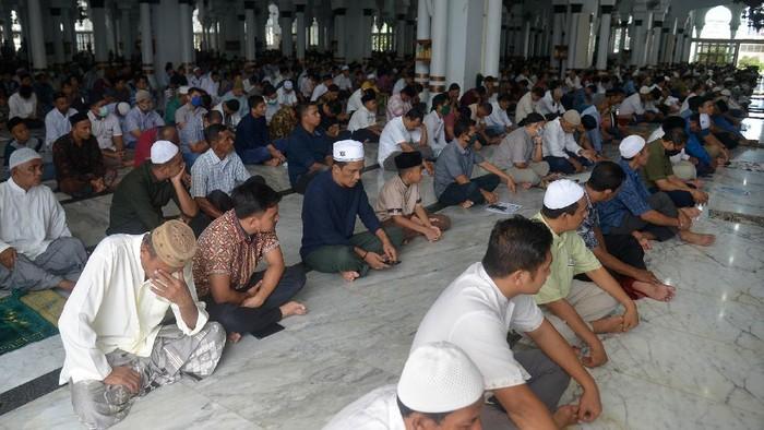 Umat muslim mendengarkan khotbah sebelum pelaksanaan shalat Jumat di Masjid Raya Baiturrahman, Banda Aceh, Aceh, Jumat (17/4/2020). Pelaksanaan shalat Jumat di Masjid Raya Baiturrahman itu tidak lagi menerapkan pembatasan jarak (physical distancing) dan hanya sebagian yang mengenakan masker. ANTARA FOTO/Ampelsa/pras.