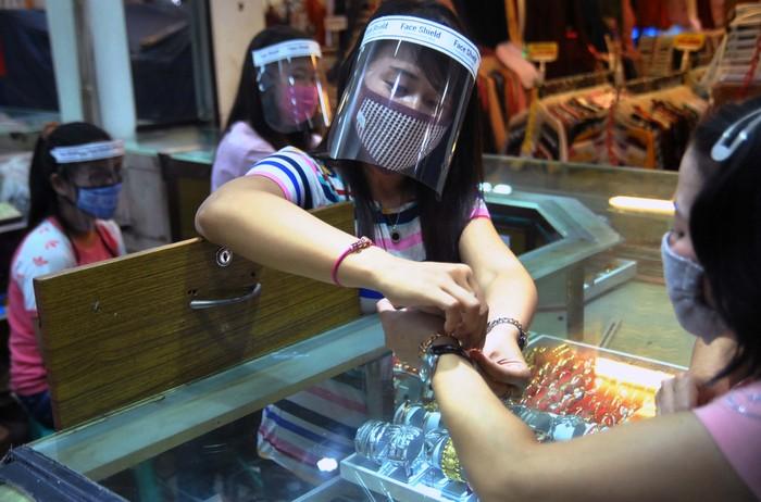 Pegawai toko menggunakan masker dan alat pelindung wajah (face shield) saat melayani pembeli di toko emas Rejeki, Pasar Bogor, Jawa Barat, Kamis (16/4/2020). Penggunaan alat pelindung wajah tersebut sebagai upaya pencegahan penyebaran wabah pandemi virus Corona (COVID-19). ANTARA FOTO/Arif Firmansyah /aww.