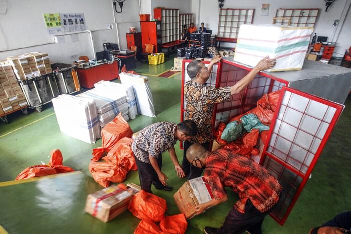 Petugas memilah paket kiriman barang di Kantor Pos, Cibinong, Bogor, Jawa Barat, Jumat (17/4/2020). Menurut petugas, dimasa penerapan Pembatasan Sosial Berskala Besar (PSBB), volume pengiriman paket pos khusus belanja online mengalami  kenaikan rata-rata 10 persen dari biasanya. ANTARA FOTO/Yulius Satria Wijaya/pras.