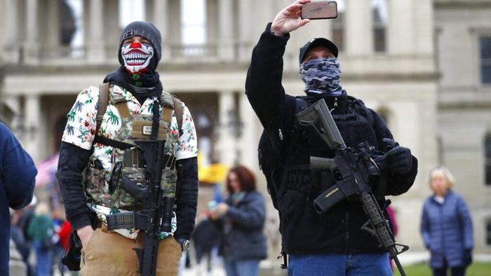 Para pendemo berunjuk rasa di depan balai kota Michigan, AS.  Mereka menentang aturan lockdown seperti tetap di rumah (stay at home) yang membuat pendemo khawatir terhadap pekerjaan dan pendapatan mereka. Aturan tersebut diberlakukan hingga 30 April mendatang.