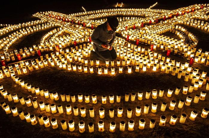Seorang warga tengah menyalakan lilin di Jerman, hal tersebut dilakukan sebagai bentuk mengenang korban yang terinfeksi virus Corona yang menyebar ke hampir seluruh penjuru dunia.