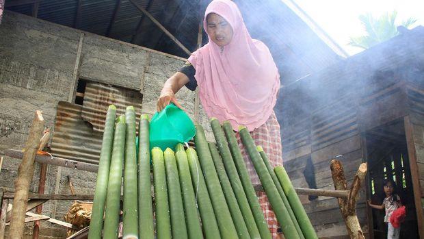 Warga memasukkan santan kelapa ke dalam bambu saat proses pembuatan lemang di Desa Alue Raya, Samatiga, Aceh Barat, Aceh, Sabtu (18/4/2020). Tradisi memasak dan membuat lemang bambu yang dilakukan secara turun temurun tersebut dilakukan dalam rangka menyambut bulan suci Ramadhan, kemudian lemang tersebut dibagikan kepada warga sekitar untuk mempererat silaturahim. ANTARA FOTO/Syifa Yulinnas/wsj.