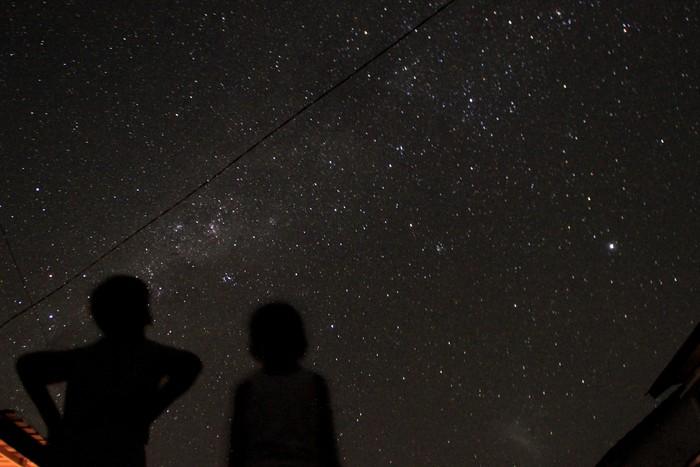 Dua bocah melihat pemandangan gugusan bintang Galaksi Bima Sakti yang terlihat di langit Kota Kupang, NTT, Sabtu (18/4/2020). Akibatnya padamnya listrik di Kota Kupang, warga pun berbondong-bondong keluar rumah untuk menyaksikan keindahan alam tersebut. ANTARA FOTO/Kornelis Kaha/wsj.