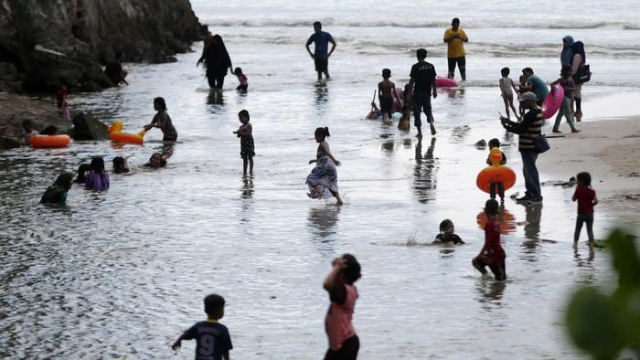 Wisatawan yang tidak mengenakan masker memadati pantai wisata Lhoknga di Aceh Besar, Aceh, Minggu (19/4/2020). Warga masih mengabaikan imbauan pemerintah untuk mengenakan masker, menjaga jarak, serta tidak berkumpul di tempat publik sebagai upaya memutus rantai penyebaran COVID-19. ANTARA FOTO/Irwansyah Putra/aww.