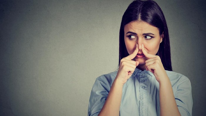 Woman pinches nose with fingers looks with disgust away something stinks bad smell isolated on gray background.
