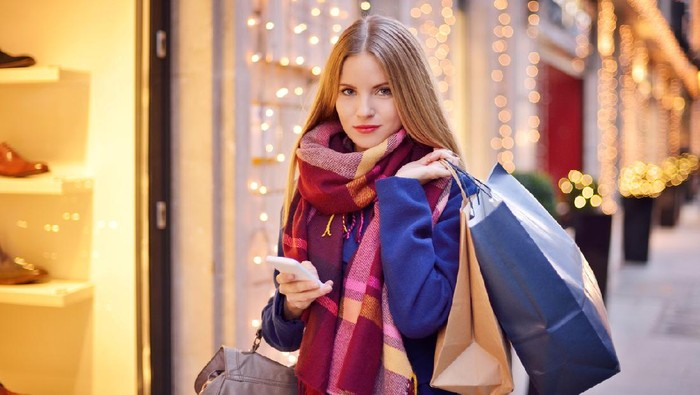 Young woman shopping in the mall and texting on mobile phone.