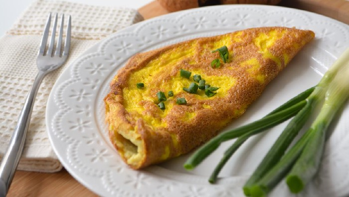 Fluffy breakfast omelette with green spring onions and fresh toast bread on a wooden surface with a napkin and metal fork