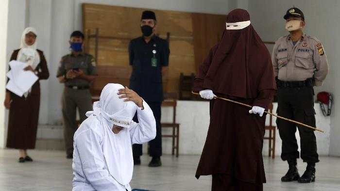 Terpidana (duduk) pelanggar hukum syariat Islam dieksekusi cambuk di Banda Aceh, Aceh, Selasa (21/4/2020). Enam terpidana pelanggar peraturan daerah (qanun) nomor 6/2020 tentang hukum jinayat tetap di eksekusi cambuk ditengah darurat pandemi COVID-19 dengan menjaga jarak sosial (phsycal distancing) dan prosedur kesehatan. ANTARA FOTO/Irwansyah Putra/hp.