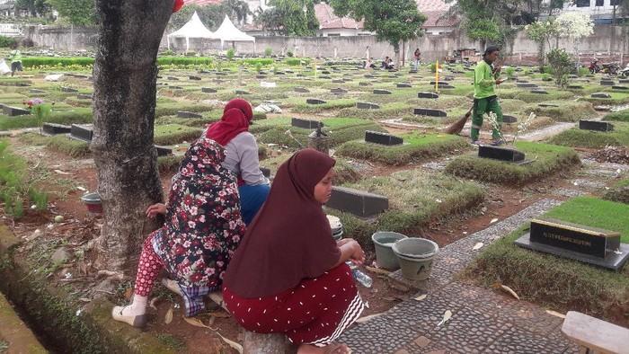 Maryah bersama rekan pembersih kubur lainnya