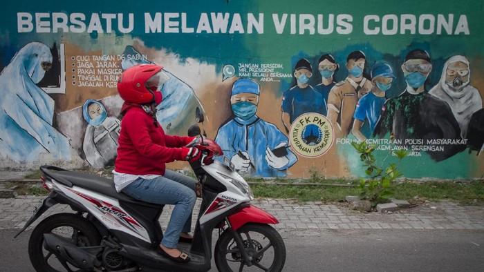 Pengendara melintas di depan mural tentang pandemi COVID-19 di Kawasan Bangil, Pasuruan, Sidoarjo, Jawa Timur, Senin (20/4/2020). Mural tersebut dibuat bertujuan untuk mensosialisasikan dan mengedukasi warga agar tetap waspada terhadap potensi penyebaran virus corona atau COVID-19. ANTARA FOTO/Umarul Faruq/wsj.