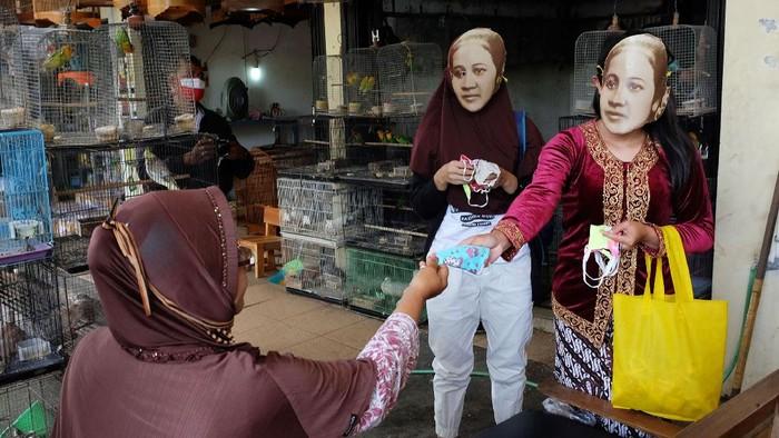 Dua wanita memakai topeng bergambar pahlawan nasional, Raden Ajeng Kartini saat membagikan masker kain di Pasar Hewan Depok, Solo, Selasa (21/4/2020). Aksi untuk memperingati Hari Kartini tersebut juga diisi edukasi penggunaan masker kain kepada masyarakat, guna mendukung pemerintah mencegah penyebaran COVID-19. ANTARA FOTO/Maulana Surya/foc.