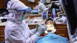 Di tengah pandemi virus Corona, dokter gigi di Jakarta ini memakai APD saat bertugas memeriksa pasien. Hal itu dilakukan guna mencegah penyebaran COVID-19.