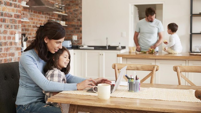 Busy Family Home With Mother Working As Father Prepares Meal