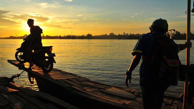Warga memanfaatkan jasa penyeberangan sepeda motor di Sungai Batanghari, Muarojambi, Jambi, Selasa (21/4/2020). Penyedia jasa penyeberangan yang melayani rute Taman Rajo-Maro Sebo tersebut mematok tarif Rp10 ribu per sepeda motor. ANTARA FOTO/Wahdi Septiawan./hp.