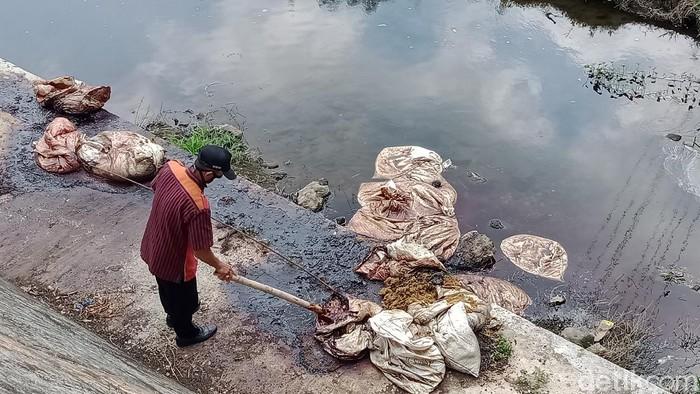 Tim Pemkab Klaten mengecek isi karung bersimbah darah di bawah jembatan Pandan Simping, Kamis (23/4/2020).