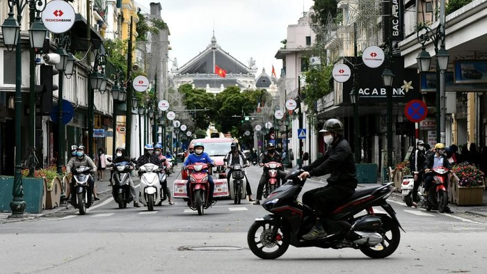 Motorists are seen at a traffic intersection in Hanoi on April 23, 2020, as Vietnam eased its nationwide social isolation effort to prevent the spread of the COVID-19 novel coronavirus. - Vietnam eased social distancing measures on April 23, with experts pointing to a decisive response involving mass quarantines and expansive contact tracing for the apparent success in containing the coronavirus. (Photo by Manan VATSYAYANA / AFP)