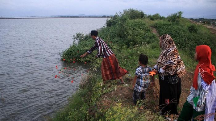 Warga korban lumpur memanjatkan doa untuk keluarga mereka yang telah wafat saat ziarah jelang ramadhan di tanggul titik 71 Tanggulangin, Sidoarjo, Jawa Timur, Kamis (23/4/2020). Mereka berdoa dari pinggir tanggul karena makam keluarganya telah tenggelam oleh lumpur. ANTARA FOTO/Umarul Faruq/aww.