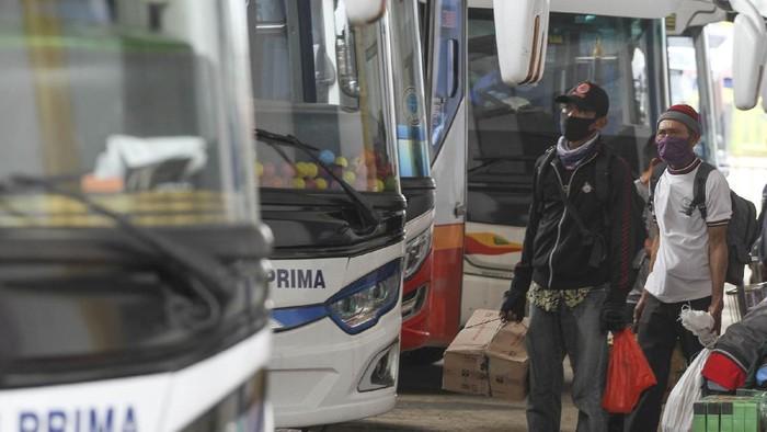 Sejumlah calon penumpang bersiap naik bus di area Terminal Jatijajar, Depok, Jawa Barat, Kamis (23/4/2020). Pemerintah memutuskan kebijakan larangan mudik Lebaran 2020 bagi masyarakat mulai berlaku Jumat (24/4) guna memutus mata rantai penyebaran COVID-19. ANTARA FOTO/Asprilla Dwi Adha/aww.